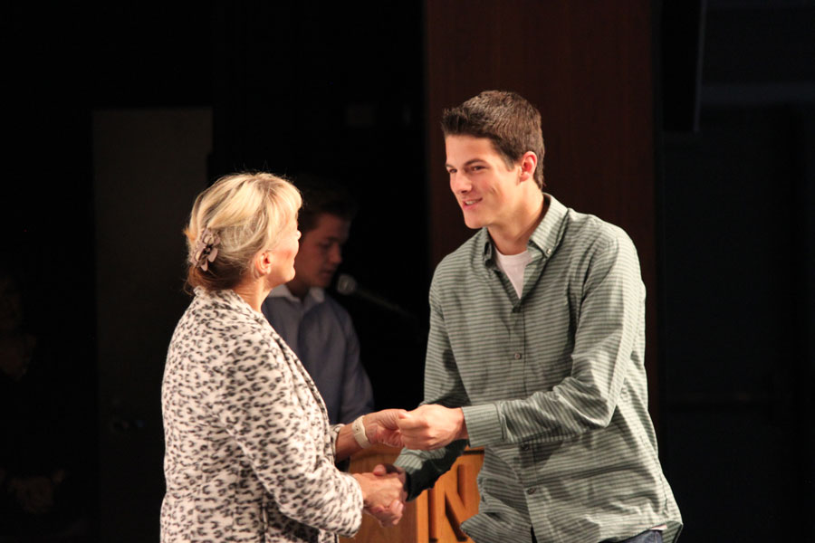 Senior Logan Frewen shakes Watts' hand as he is given his third year academic award pin.