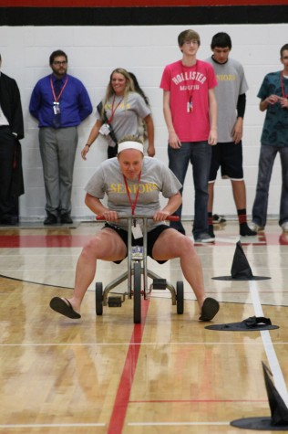 Megan Rose racing on a tricycle during homecoming assembly.
