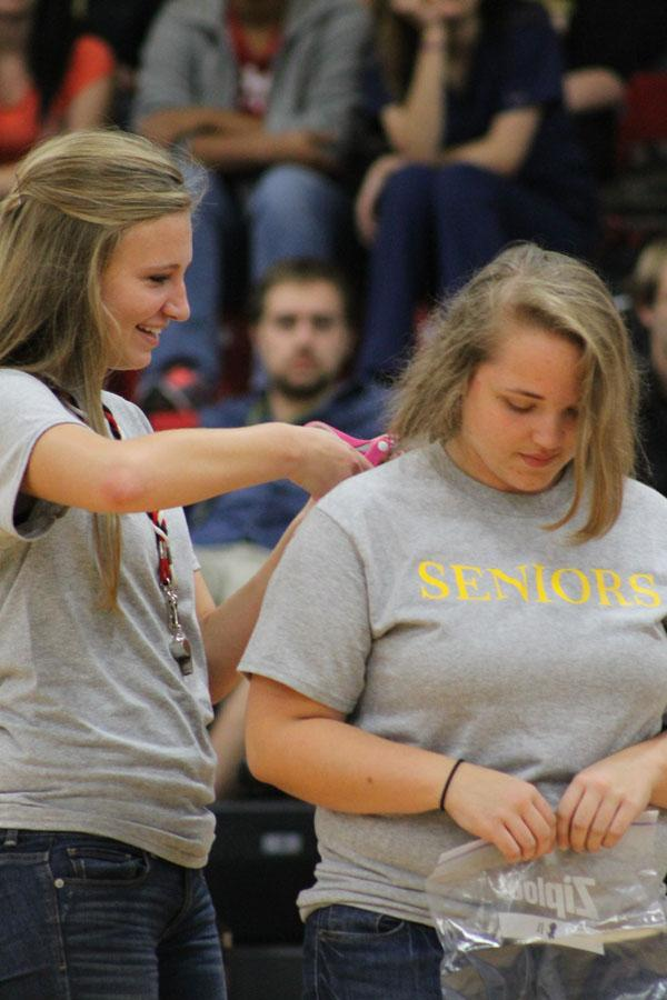 Senior Jaynie Sorenson cuts Paige Beverage so she can donate her hair