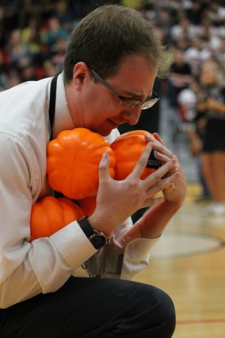 Mr.  Snell  competing in the pumpkin race during the homecoming assembly