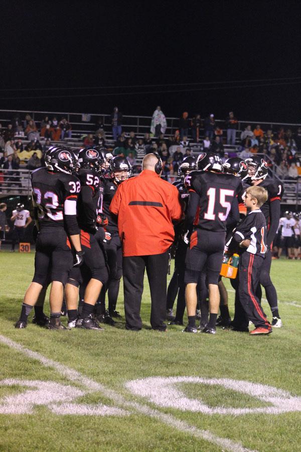 Varsity+football+team+huddles+before+play.