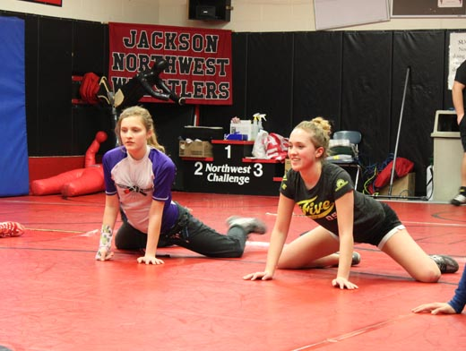 Freshman Sydney Boulter and junior Faith Boutler, sisters, stretch with the wrestling team before practice.