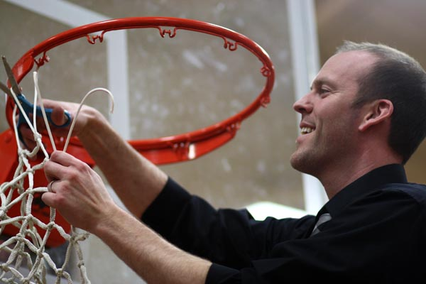 Coach Carroll cuts down the net after winning districts
