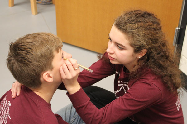 Sophomore Chris Boyer is helped with makeup by  Sophi Epstein.