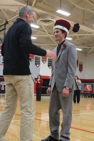 Principal Scott Buchler congratulating senior Jacob Phelan on becoming Snowfest King.