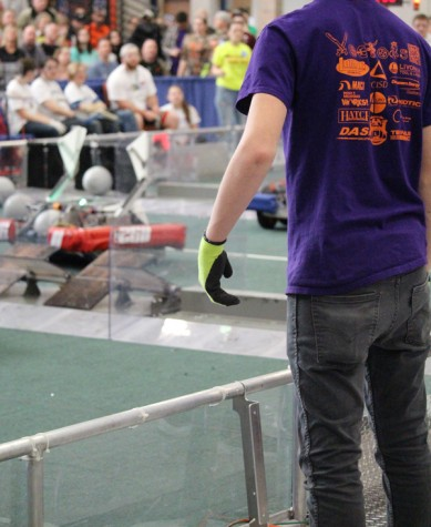 Senior Aaron Heath is spying to the drive team to direct the robot.