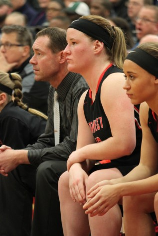 Assistant Coach Mr. Jason Khon and seniors Sarah Gwinn and Tyriah Pryor watch from the sidelines.