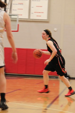 Senior Lexie Khon dribbles the ball in the perimeter.