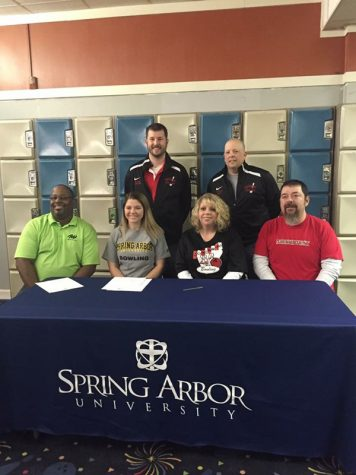 Senior Kelsey Thomas being supported by her parents, high school coaches, and college coach at her signing.