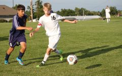 Freshman Joe Frederickson attempts to kick the ball away from opposing team.