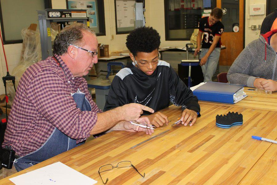 Rossner helps sophmore Tahj Swanson layout a keychain in STEM Advanced Manufacturing and Engineering.