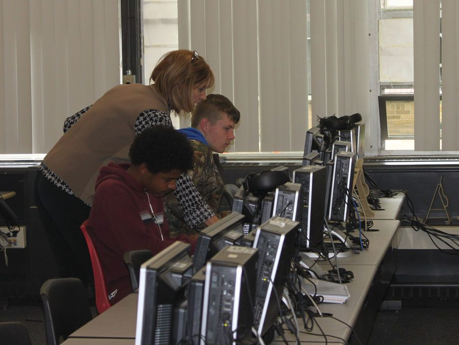 Accounting teacher Mrs. Janie Chase helps two students with their e2020 classes in the computer lab.