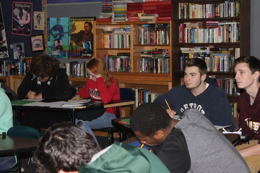 Two students watch English teacher Mrs. Kim Csage in Literature class.