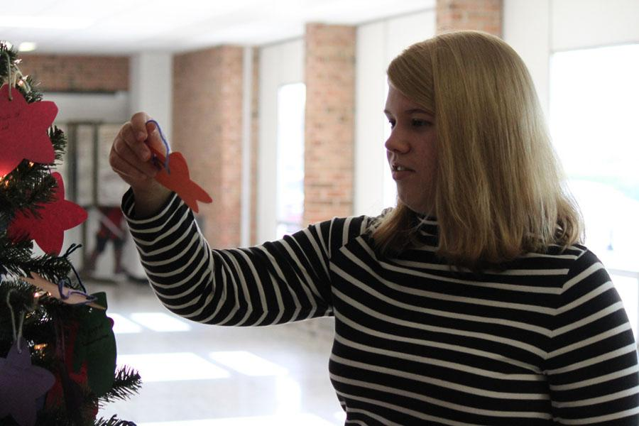 Senior Rachael Kaiser takes an ornament off of the giving tree for Adopt-a-Family.