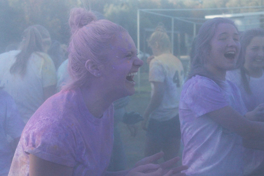 Senior Ella Bontrager laughs after she throws powdered chalk at a friend.