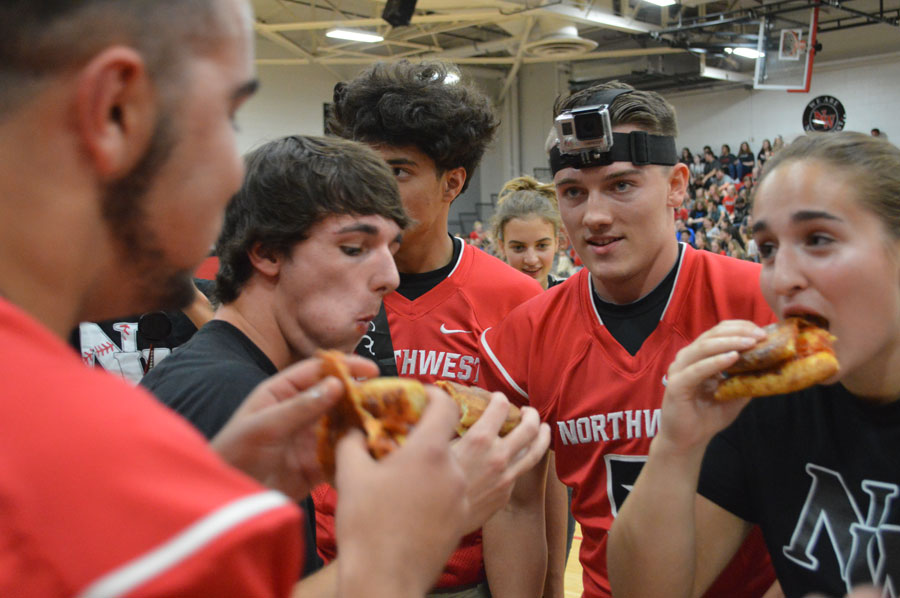 Seniors Cyle Risniger, Courtney Johnson, and Damian DeLattre eat Klavons pizza during the pizza relay. Seniors Diego Wolfe and Jason Shepherd stand by, giving words of encouragement.