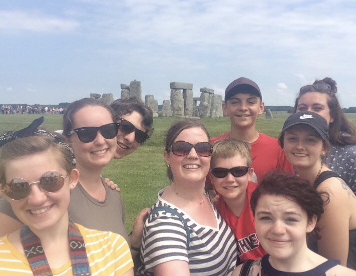Teacher Mrs. Dryer takes a group selfie with members travel club at Stonehenge, England.