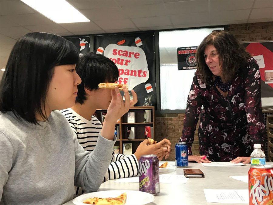 Senior Shiori Ogata eats Marino's pizza with her fellow new students and Ms. Judy Scott during the new student lunch in the library on Oct. 12. Ogata explains how pizza is different in her home country of Japan.