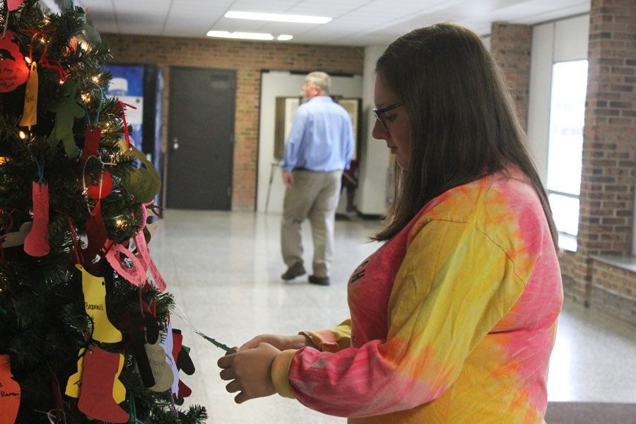 Senior Sydney Bowler takes ornaments from the giving tree to help a family in need.