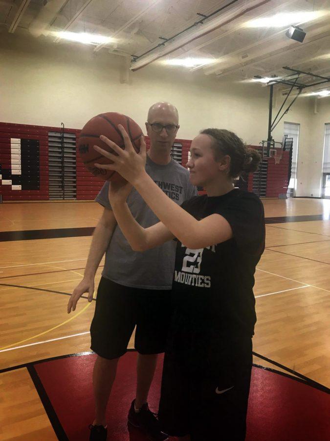 Coach Chris DeBacker assists freshman Lucy Nurkka in lining up a shot.