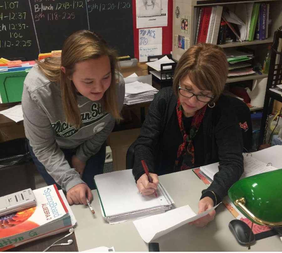 Johangten assists junior Madelyn Atwood on a work problem that she has questions on.