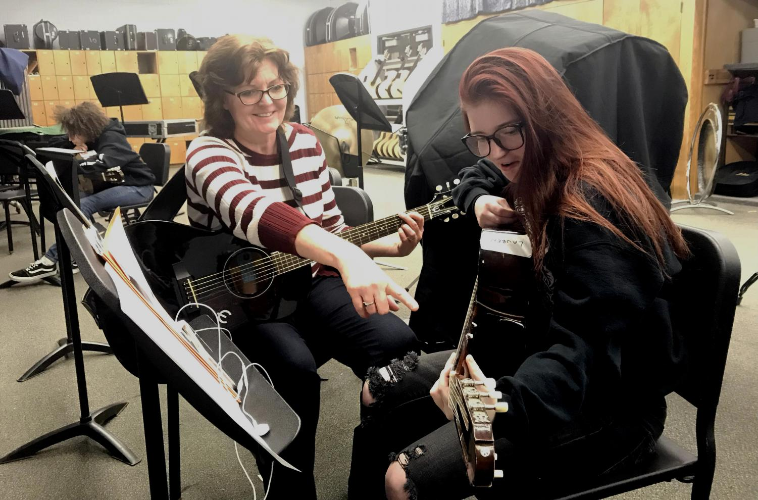 Community member Janet Belding assists sophomore Lauren Ingram in correct finger placement for a guitar note.